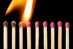 Line of matches igniting one by one. Burning matches on the black background