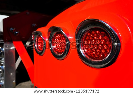 Line of rear round red marker lights with chrome rims on fender of red big rig semi truck shining on the sun