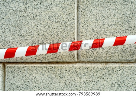 Line of red warning tape used for hazards and awareness set against a grey brick wall background with nobody in the scene. Copy space area for security and warning based designs and ideas #793589989