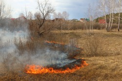 Line of the fire coming toward the village - burning meadow grass