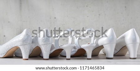 Line of three pairs of stylish white high heel shoes viewed from the back with the center pair having straps in a concept of wedding fashion with copy space above in panorama view #1171465834