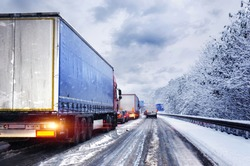 Line of trucks waiting on a german highway due to snow fall and ice on streets