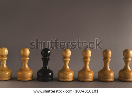 Line of white pawns with one black inside. Uniqueness of individuals in mass, loneliness concept
