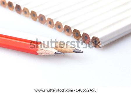 Line of white pencils with red and white pencils out the line