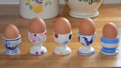 Line up of five boiled eggs in fun, colourful china egg cups all of different designs. All resting on a  bright wood worktop, the base of two pottery containers are in view behind.