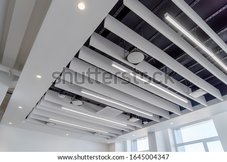 Photo of  linear LED lights and sound absorbing ponies hang on a plasterboard ceiling with integrated spotlights