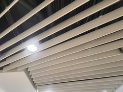 Linear open cell ceiling for decorative with shining light bulb, selective focus