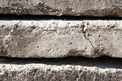 Linear texture of gray concrete slabs block with a crack stacked on top of each other close-up side view. Grunge, material aged, construction. Brutal background