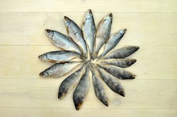 Lined dried fish pattern on a wooden surface. Dried fish product background texture. Food