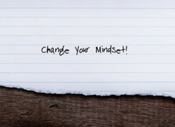 Lined sheet paper on old vintage wood background with handwritten text CHANGE YOUR MINDSET , concept of level up belief system or mindset to achieve goals or success