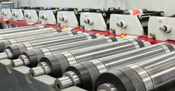Lined up magnetic cylinders for die cut on rotary printing press. Magnetic cylinder for flexo rotary die cutting. Magnetic roll and in-line press machine in background. Cylinder for cutting dies.