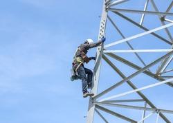 Lineman climbing on transmission line tower