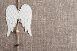 Linen background with christmas decoration. Angel wings toy. Wedding, xmas rough texture flat lay