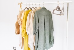 Linen clothes on gray hangers on the clothes rack. Slow Fashion. Conscious consumption. Crisis in the fashion industry, retail. Eco-friendly, Sustainable seasonal Sale concept. Zero waste.