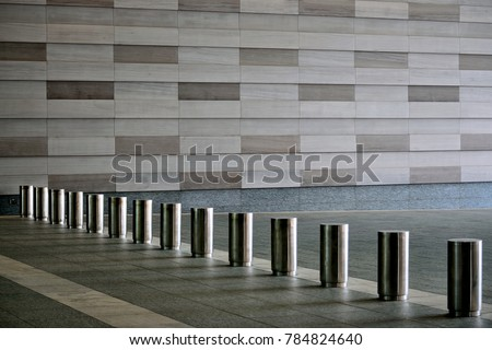 Lines of stainless steel bollards in the modern entrance of an office building in the Business District, Singapore