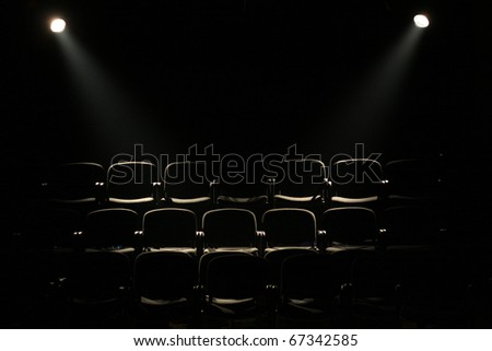 lines of theater chairs in darkness with two reflectors