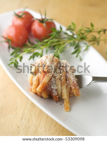 Linguine in tomato sauce and Parmesan, coiled around fork on tasting plate with fresh herbs and cherry tomatoes in background.