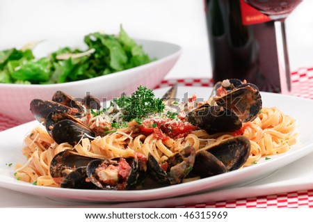 Linguini with baby clams and fresh mussels in tomato sauce with parmesan cheese and fresh herbs, accompanied buy lettuce salad and red wine