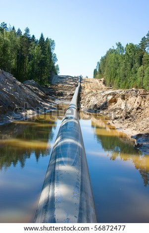Lining of the long pipeline on a countryside,  flood by water - stock photo