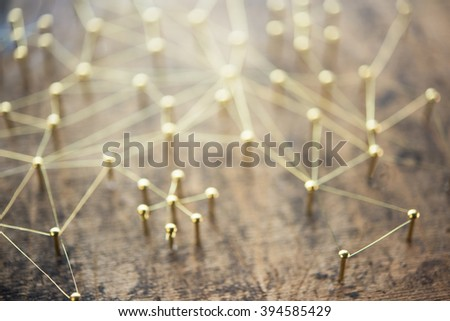 Linking entities, blurred background, or off-focus background. Network, networking, social media, internet communication abstract. Web of gold wires on rustic wood.