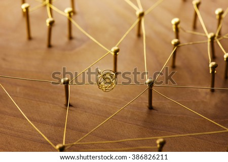 Linking entities. Dispute or conflict, or Bottleneck  between two entities. Network, networking, social media, internet communication abstract. Web of gold wires on rustic wood.
