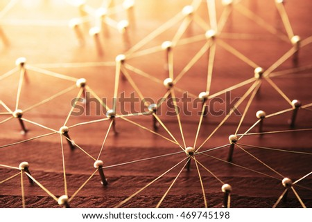 Linking entities. Network, networking, social media, internet communication abstract. Web of gold wires on rustic wood. Shallow depth of field. Intentionally shot in surreal tone.