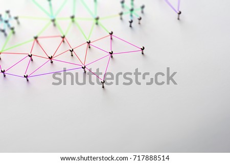 Linking entities. Networking, social media, SNS, internet communication abstract. Small network connected to a larger network. Web of red,orange green and blue wires on white background. Shallow DOF.