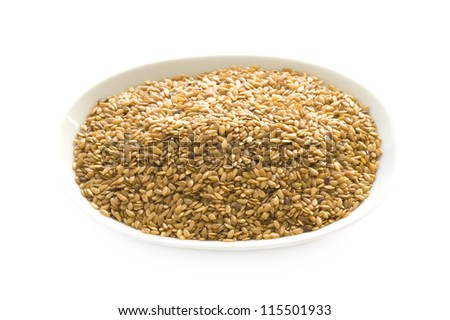 linseed or flaxseed in a dish isolated on a white background