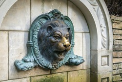 Lion head fountain on the wall. Vintage brick wall texture with lion shaped stucco. The molded face of a lion is sprayed with water. Bas-relief lion fountain