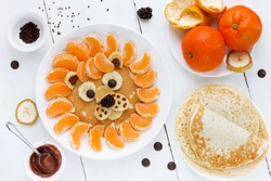 Lion pancake with tangerines chocolate banana berry. Fun food for kids, funny and healthy pancake for breakfast