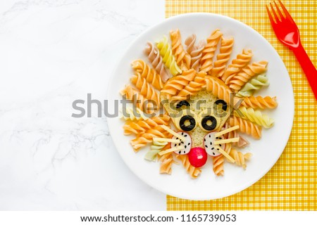 Lion pasta - fun food idea for kids lunch, animal shaped food art. Colorful fusilli vegetables pasta with sandwich like a cute lion head on white plate top view