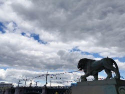 Lion sculpture on the background of the Palace Bridge, decorated with flags for the Navy Day.