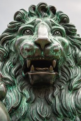 Lion statue aged. Close up of the head of a bronze sculpture of a lion. Large bronze lion statue sculpture in outdoor setting.