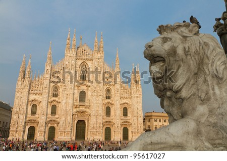 Lion statue in the Piazza del Duomo with cathedral at sunset  Milan, Italy