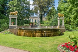 Lions Fountain, a symbol for Park Glienicke, with its two gilded cast-iron sculptures of Medici lions spouting water, flower bed, the balustrade and the palace in the background