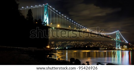 Lions Gate Bridge over Burrard Inlet in Vancouver BC Canada at Night Panorama