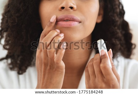 Lip Care. Unrecognizable black woman applying moisturising chapstick on lips, cropped image, closeup Stockfoto ©