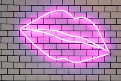 Lip shaped neon signs led glow decorative lights, wall decor. Purple fluorescent lamps on tiled white brick wall.