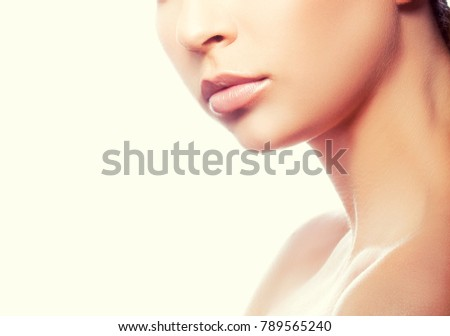 Lips and part of face of young model girl with natural nude make-up, pale lips and perfect skin. Youth and skincare treatment beauty style #789565240