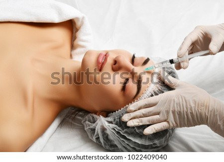 Lips cosmetology plastic surgery beauty concept young brunette woman face and  doctor hand in glove with syringe making injection #1022409040