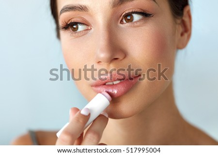 Lips Protection. Beautiful Woman With Beauty Face, Sexy Full Lips Applying Lip Balm, Lipcare Stick On. Portrait Of Female Model With Natural Makeup. Lips Skin Care Cosmetics Concept. High Resolution #517995004