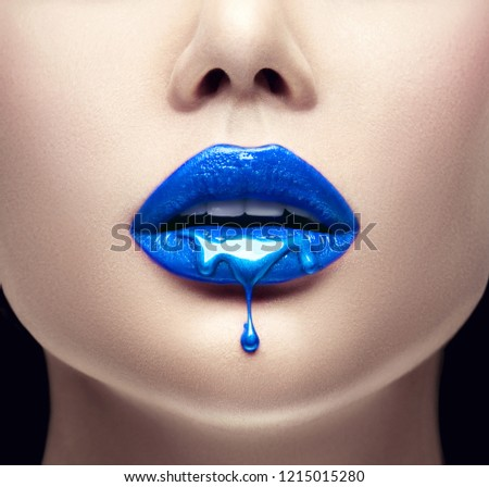 Lipstick. Blue Paint drips from the lips, lipgloss dripping from sexy lips, blue liquid drops on beautiful model girl's mouth, creative abstract blue make-up. Beauty woman face makeup close up