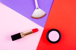 Lipstick, eye shadow and brush in bright fashion background. Pink, red and fuchsia makeup