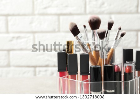 Lipstick holder with different makeup products on table against brick wall, closeup. Space for text #1302718006