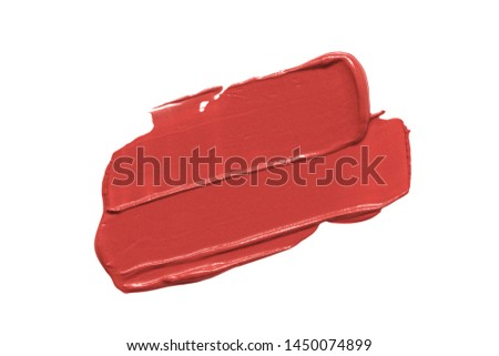 Lipstick smear smudge swatch isolated on white background. Cream makeup texture. Bright color cosmetic product stroke swipe sample. Warm red autumn tone
