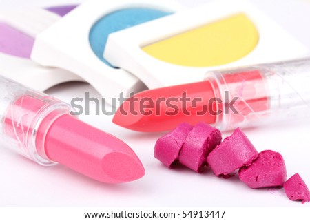 Lipsticks and eyeshadows, closed-up on white