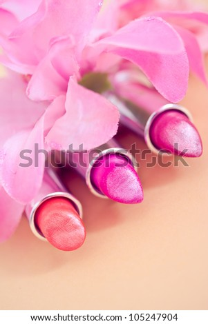 lipsticks colors with petals in the background