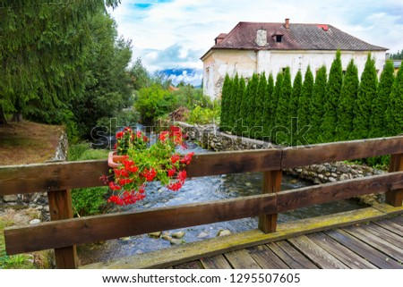 Liptovsky Jan spa village at summer: view of the stone embankment and fast mountain river from the wooden bridge. Slovakia. Tourist attraction, tourist destination, spa vacation #1295507605