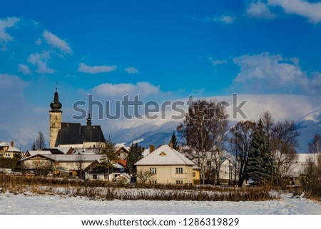 Liptovsky Jan village at winter: houses and an ancient church on the background of mountains and a blue cloudy sky. Slovakia. Tourist attraction, tourist destination, spa vacation #1286319829