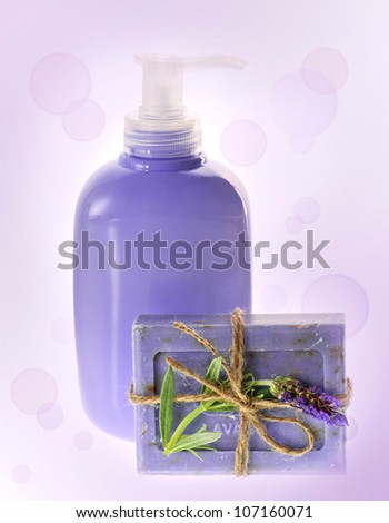 liquid and bar of lavender soap on blurred background